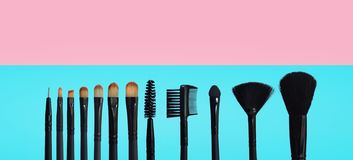 Set of makeup brushes on colored composed background. Set of makeup brushes on pink, blue colored composed background, isolated white royalty free stock photography