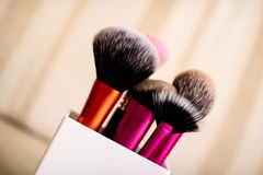 A set of makeup brushes in a plastic white glass royalty free stock photo