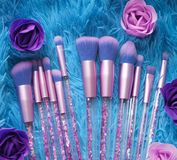 Set of makeup brushes with sparkles on pink, lilac and blue colored composed background Royalty Free Stock Photos