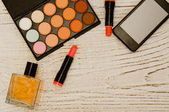 Set of makeup, eye shadow, lipstick, perfume, smartphone. Space for text. Wooden background Royalty Free Stock Photography