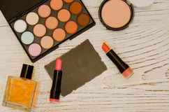 Set of makeup, eye shadow, lipstick, powder, perfume, label for text. Wooden background Stock Images