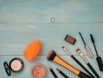 Set of makeup on turquoise wooden background. Set of make up on turquoise wooden background. Mascara brush, eyebrow gel brush, pencil, eyeshadow, sponge and Royalty Free Stock Images