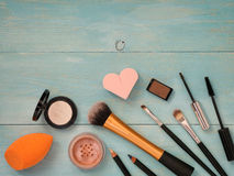 Set of makeup on turquoise wooden background. Set of make up on turquoise wooden background. Mascara brush, eyebrow gel brush, pencil, eyeshadow, sponge and Royalty Free Stock Photography