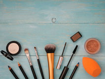 Set of makeup on turquoise wooden background. Set of make up on turquoise wooden background. Mascara brush, eyebrow gel brush, pencil, eyeshadow, sponge and Royalty Free Stock Photos