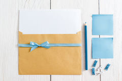 Set for making handmade greeting card, flat lay. Top view on kit of envelope with blank paper and blue ribbon, pencil, pins and sticker on white background. It Royalty Free Stock Image