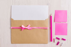 Set for making handmade greeting card, flat lay. Top view on kit of envelope with blank paper and pink ribbon, pencil, pins and sticker on white background. It Royalty Free Stock Photos