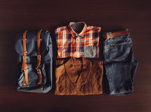 Set of male clothing in hipster style. Set of male clothing and backpack in hipster style on wooden background, top view Royalty Free Stock Photos