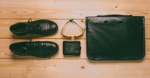 Black leather shoes, black leather wallet, sunglasses and black leather briefcase on wooden background, top view. Set of male items: black leather shoes, black Stock Images