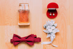 Set of man's and woman's accesories on rustic wooden background. Perfume, burgundy bow-tie, red box with pearl decorated Royalty Free Stock Images