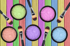 Set of many eyeshadows and brushes on painted color wooden Royalty Free Stock Image