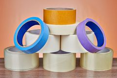 Set of masking tape is stacked in form of pyramid. Set of scotch packing tape is stacked in form of pyramid, on orange background Royalty Free Stock Images