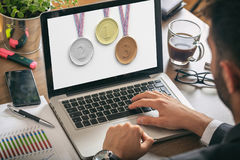 Set of medals on a laptop screen - man at work Stock Photos