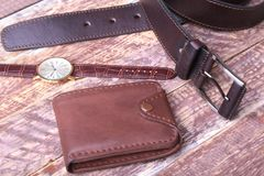 Set of men`s accessories for the business with leather belt, wallet, watch and smoking pipe on a wooden background. The. Concept of fashion and travel Royalty Free Stock Photo