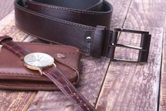 Set of men`s accessories for the business with leather belt, wallet, watch and smoking pipe on a wooden background. The. Concept of fashion and travel Stock Image