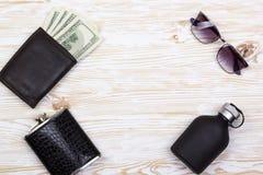 Set of men's accessories: wallet, flask, sunglasses and perfume. Set of men's accessories: wallet with dollard, flask, sunglasses and perfume on wooden Stock Image