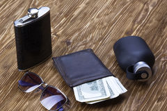 Set of men's accessories: wallet, flask, sunglasses and perfume. Set of men's accessories: wallet with dollard, flask, sunglasses and perfume on wooden Royalty Free Stock Photos