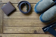 Set of men`s clothing and accessories. Shoes, belt, wallet and p. En on wooden table. Top view with copy space Stock Photo
