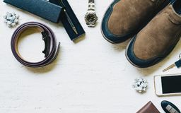 Set of men`s clothing and accessories. Shoes, belt, wallet, watc. H, mobile phone, car key and pen on grungy white wooden table background. Top view with copy Stock Photography