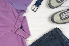 Set of men's clothing and shoes on wooden background. Sports T-shirt and sneakers in bright colors. Top view Stock Photos