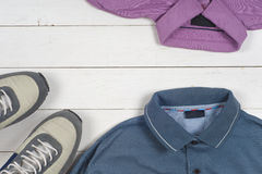 Set of men's clothing and shoes on wooden background. Sports T-shirt and sneakers in bright colors. Top view Stock Images