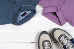 Set of men's clothing and shoes on wooden background. Sports T-shirt and sneakers in bright colors. Top view Stock Image