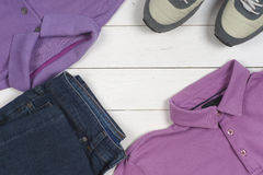 Set of men's clothing and shoes on wooden background. Sports T-shirt and sneakers in bright colors. Top view Royalty Free Stock Image