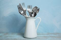 Set of metal cutlery in jug on table Royalty Free Stock Images