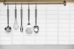 Set of metal kitchen utensils hanging. On wall stock photography