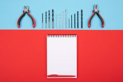 Set of metalwork tools with notebook and pen on colorful background stock photography