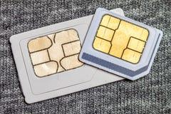 Set mini i mikro simcard Odizolowywający na popielatych sukiennych tekstura półdupkach zdjęcie stock