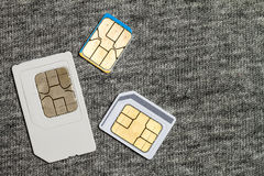 Set of mini, micro and nano simcard.  on grey cloth text. Ure background Royalty Free Stock Photos