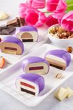Set of violet heart shaped mousse cakes with various fillings. royalty free stock photography