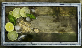 Set for Mojito - limes, mint and ice in frame. Set for Mojito - limes, mint leaves and ice in the old frame on the wooden background royalty free stock image