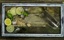 Set for Mojito - limes, mint and ice in frame. Set for Mojito - limes, mint leaves and ice in the old frame on the wooden background stock images
