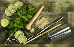 Set for Mojito - limes, mint leaves, hammer. On the wooden background royalty free stock photography