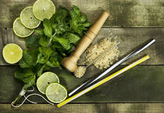 Set for Mojito - limes, mint leaves, hammer. On the wooden background royalty free stock image