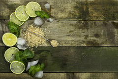 Set for Mojito - limes, mint leaves and ice. On the wooden background royalty free stock photo