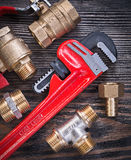 Set of monkey wrench brass connectors water valve on wooden boar Royalty Free Stock Image