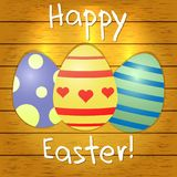 Set of multi-colored Easter eggs on a brown wood texture background. Happy easter. Royalty Free Stock Images