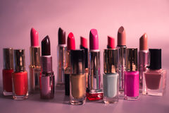 Set of multi-colored lipsticks and nail polishes on a pink background Royalty Free Stock Photo