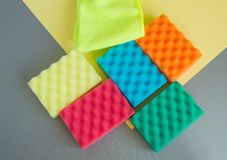 A set of multi-colored sponges and rags for cleaning and cleanliness on a gray background, the concept of outsourcing. Cleaning company, top View, flat lay stock images
