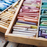 Set of multicolored pastel crayons in open wooden artist box. On rustic desk. Selective focus Royalty Free Stock Photography
