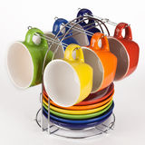 Set of multicolored teacups and saucers on stand. Isolated on white background Stock Photo