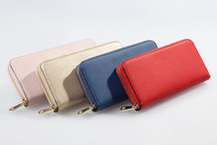 Set of multicolored women`s wallets. Four multicolored female purses lined up in a row on a white background Stock Images