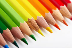 Set of multicoloured pencils lying on white table Royalty Free Stock Images