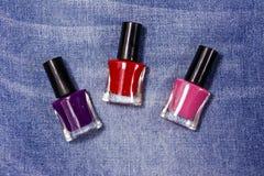 Set of nail polish bottles on jeans background stock images