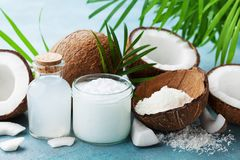 Set of natural coconut products for spa treatment, cosmetic or food ingredients decorated palm leaves.Coconut oil, water, shavings royalty free stock photos