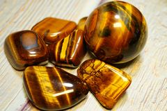 Set of natural mineral gemstones of a certain type. Tiger Eye Semiprecious Gemstone Birthstone on a wooden table. A collection of. Beautiful gemstones minerals stock image