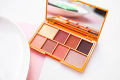 Set of natural warm eyeshadows with a mirror. Eye shadow of crimson shade on white background. The concept of makeup and office dresscode. nude palette of stock images