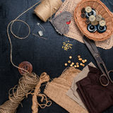 Set for needlework: scissors, linen fabric with a rope on black background. Top view. Stock Photography